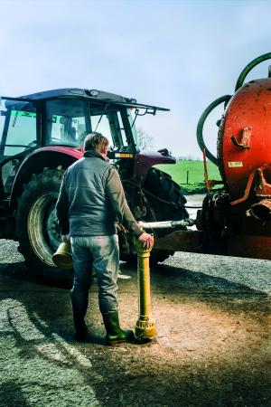 Image showing a farmer standing in front of a tractor