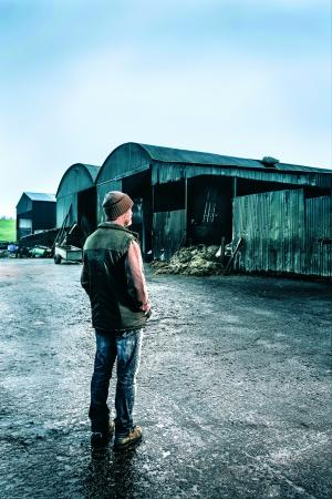 Image of a farmer standing in front of a tall shed